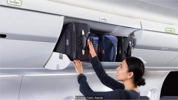 Pasajera guardando equipaje en el compartimento superior de un avión.