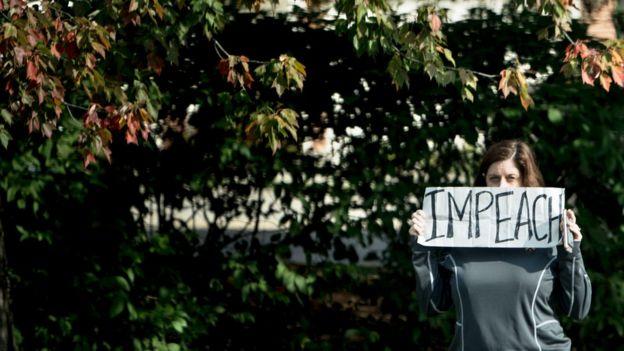 Una mujer sostiene un cartel con la palabra Impeach.