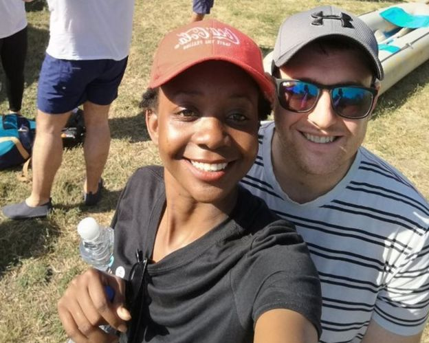 Zanele and Jamie take a selfie in front of a canoe