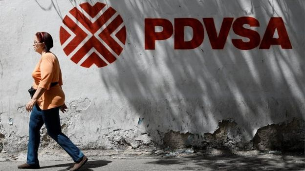 A woman walks past a mural with the corporate logo of the state oil company PDVSA in Caracas, Venezuela November 3, 2017