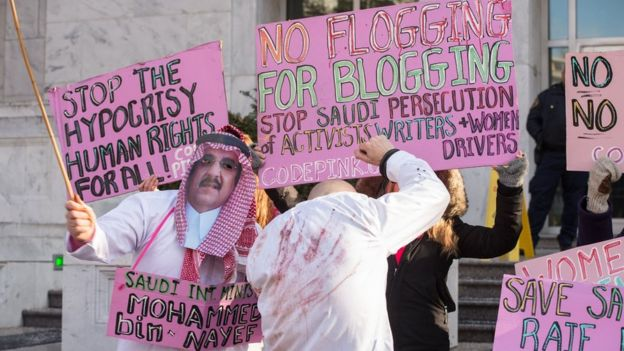 Protesters simulate a flogging in front of the Saudi embassy in Washington,DC on January 15, 2015 during a demonstration against the 10-year prison sentence and 1,000 lashes of Saudi activist Raef Badawi for 'insulting Islam' in a blogpost