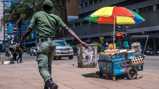 A Zimbabwean soldier walks by a street vendor in Harare's Central Business District main streets on 20 November 2017