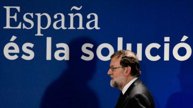 """Rajoy caminando tras un letrero que dice """"España es la solución"""" en catalán"""
