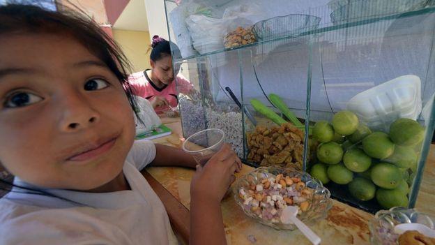 Niña peruana comiendo.