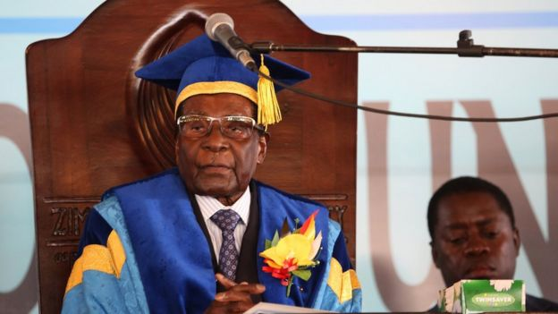 Mr Mugabe in wooden high-backed chair with microphone in front of him but above his mouth level