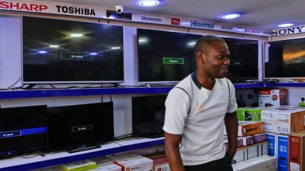 A Kenyan electronics dealer stands by blank screens that should be playing the three suspended channels