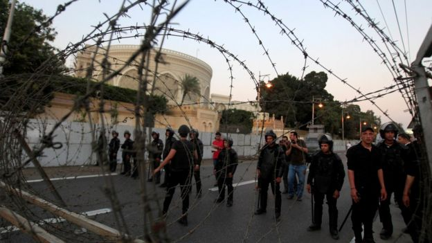 File photo of riot police standing behind a barricade near the Ittihadiya presidential palace in Cairo (26 April 2014)