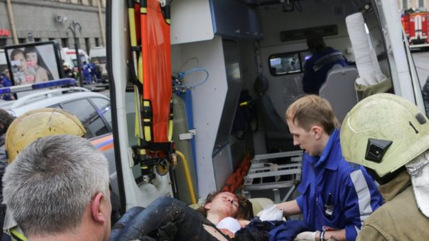 An injured person is helped by emergency services outside Sennaya Ploschad metro station, following explosions in two train carriages at metro stations in St Petersburg,
