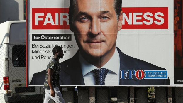 A man walks past an election campaign billboard that shows Heinz-Christian Strache of the far-right FPO