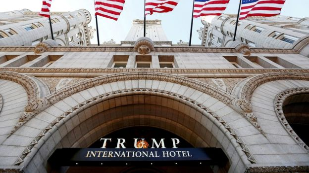 Banderas flamean sobre la entrada al nuevo hotel internacional de Trump en su día de la inauguración en Washington D.C.