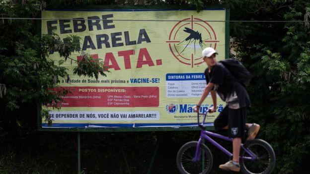 Homem passa em frente a placa que diz 'Febre amarela mata'