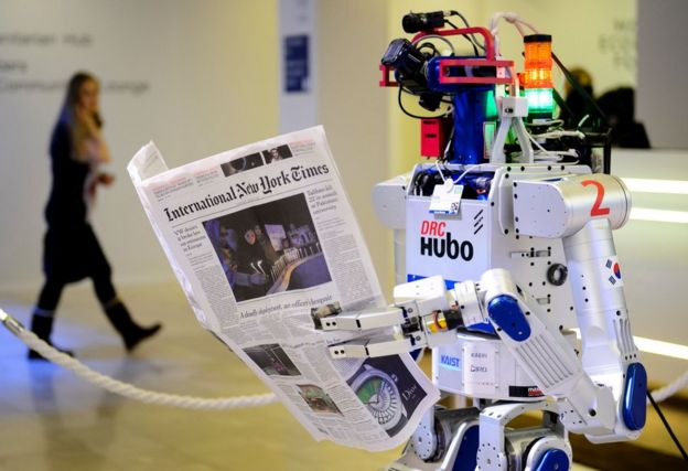 A robot holds a newspaper during a demonstration during the World Economic Forum (WEF) annual meeting in Davos, on January 22, 2016.