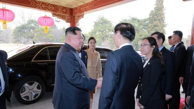 Kim Jong-un stands in front of his Mercedes Benz car in Beijing