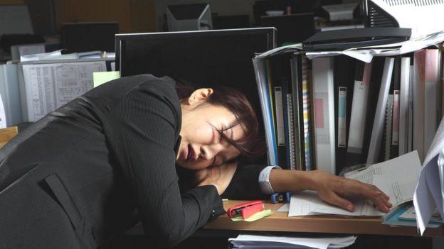 Mujer de rasgos asiáticos dormida sobre el escritorio de la oficina.