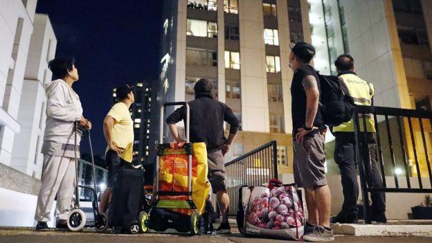 Kule bloklarına bakan insanlar