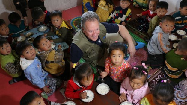 David Beasley surrounded by children in North Korea