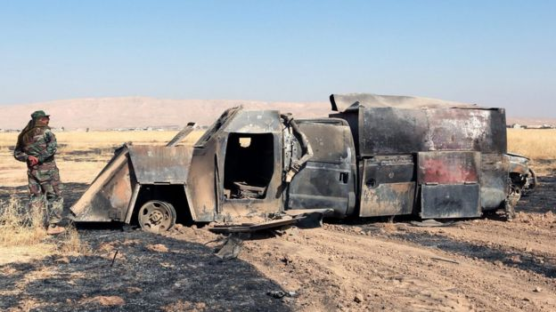 A Kurdish fighter inspects a charred truck used by Islamic State militants east of Mosul, Iraq, 18 October 2016