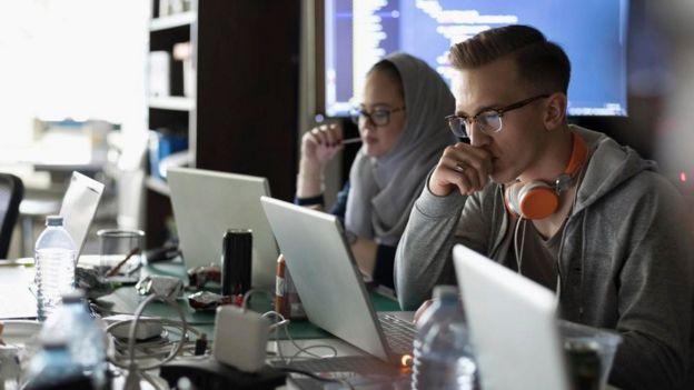Unas personas trabajando frente a sus computadoras
