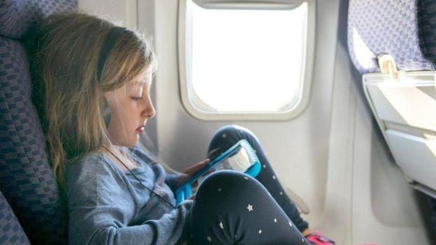 Una niña con una tableta en un avión