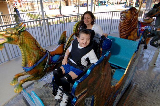 轮椅上的一个小男孩喜欢旋转木马