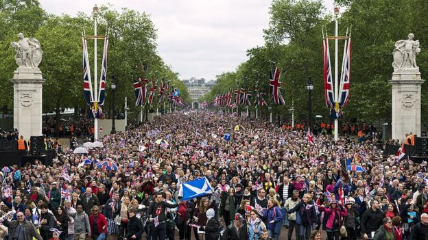 Huge crowds cheering with Britain's Union flags march down the Mall towards Buckingham Palace to celebrate the Queen's Diamond Jubilee