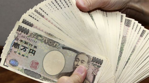 A man holds a pile of 10,000 yen notes.