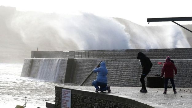 People watch waves crashing against the seafront in Auderville, Normandy, as storm Eleanor hits the northern part of France on 3 January 2018