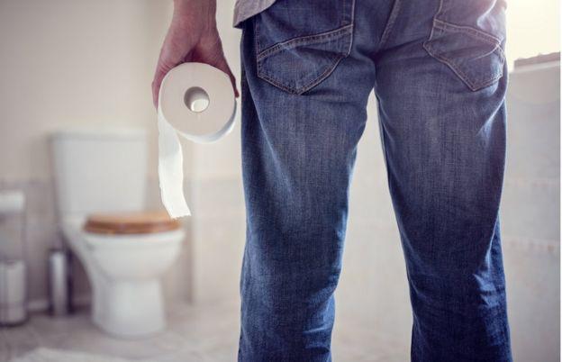 Un hombre sostiene un rollo de papel de baño.