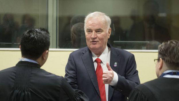 Ratko Mladic dando un apretón de manos a sus abogados defensores antes del inicio de la audiencia