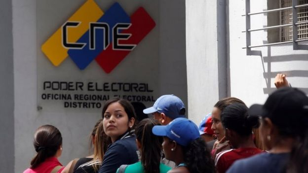 People gather outside a validation centre during Venezuela's CNE second phase of verifying signatures for a recall referendum against President Maduro, in Caracas, Venezuela, June 24, 2016.