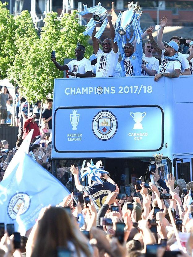 Manchester City's midfielder Fabian Delph holds up the Premier League trophy