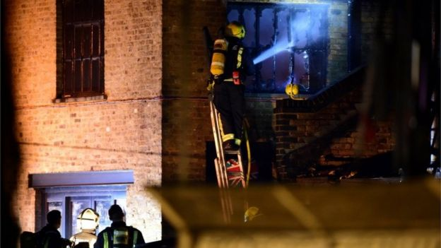 Firefighter aiming hose at burned-out window
