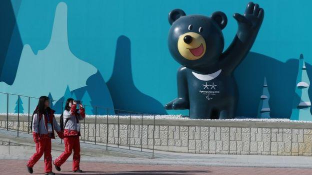 Voluntarias pasan frente a una escultura de una mascota de las Olimpiadas de Invierno en el Parque Olímpico Gangneung, en Gangneung, Corea del Sur.