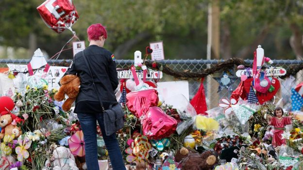 A Marjory Stoneman Douglas High School student stops to look at one of the memorials following their return to school in Parkland, Florida on February 28, 2018