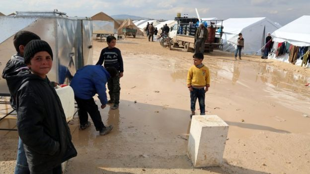 Photo provided by Turkish aid group IHH shows displaced Syrians outside tents at a new temporary camp in Haramein in Syria, near the border with Turkey (11 February 2016)