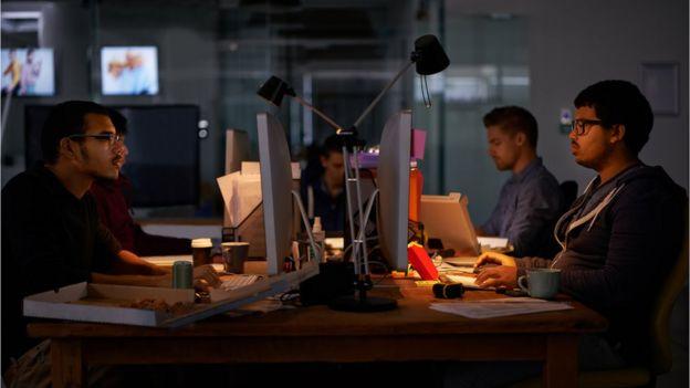 Hombres trabajando en computadoras (crédito: iStock)