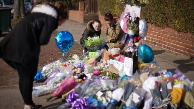 Photos, tributes and toys and flowers at the scene