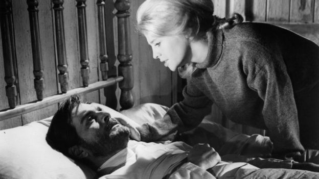 "Omar Sharif laying in bed as Julie Christie bends to his bedside to comfort him by touching his cheek in a scene from the film ""Doctor Shivago"", 1965"