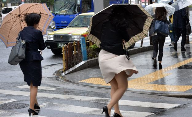 Women struggling to hold umbrellas in high winds and rain in Tokyo