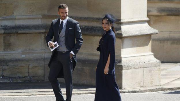 David Beckham e Victoria Beckham chegam à capela de São Jorge. Ele veste fraque, com colete cinza claro; ela, um vestido azul marinho na altura da canela, com chapéu