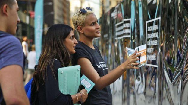 Jóvenes que miran una instalación de Talkspace, con espejos estilo feria