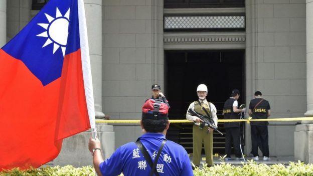 Un manifestante com uma bandeira de Taiwan em frente a um edifício oficial en Taipei