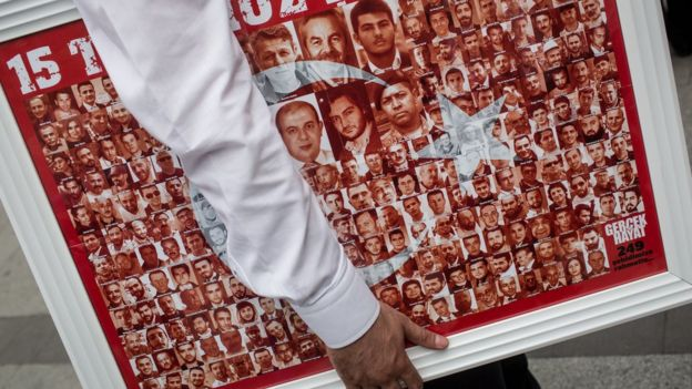 photos making up the Turkish flag, on a poster under someone's arm