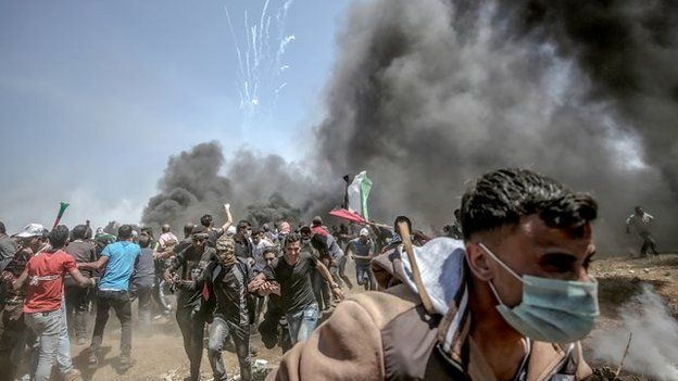 Palestinian protesters run for cover from Israeli tear-gas during clashes after protests near the border with Israel in the east of Gaza Strip,