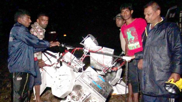 Sri Lankan men at a tea plantation look at the wreckage of a Google balloon that crashed in the central part of the country in Gampola on February 17, 2016