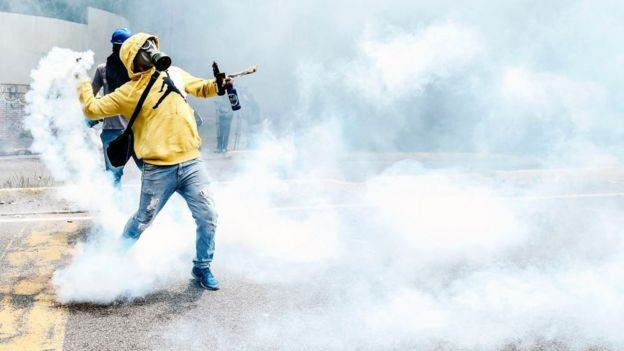 Un opositor venezolano relanza una bomba de gas lacrimógeno durante una protesta contra Nicolás Maduro el 1 de mayo en Caracas.