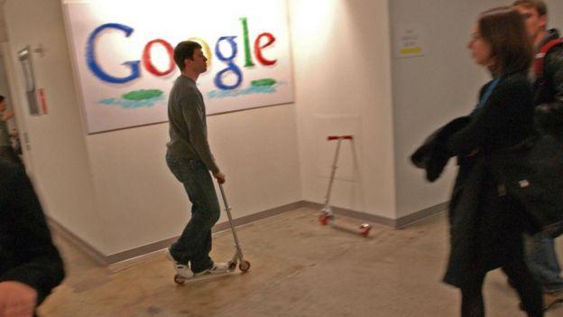 Un empleado de Google cruza la oficina en un monopatín