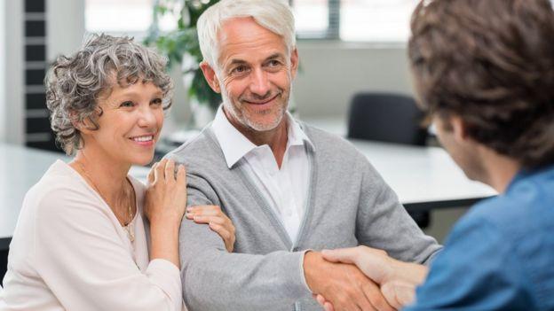 Casal de idosos conversa com uma pessoa