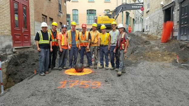 Workers pose beside the cannonball in Quebec