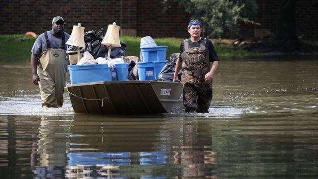 Dos hombres llevan una lancha con víveres durante la tormenta Harvey.